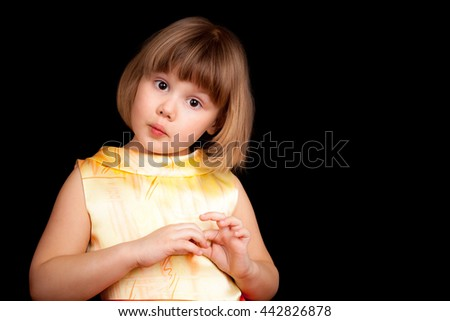 Studio portrait of funny little Caucasian blond girl on black background - stock photo