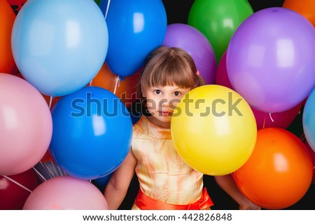 Studio portrait of funny little Caucasian blond girl with colorful balloons on back background