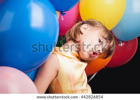 Studio portrait of funny little Caucasian blond girl with colorful balloons over back wall - stock photo