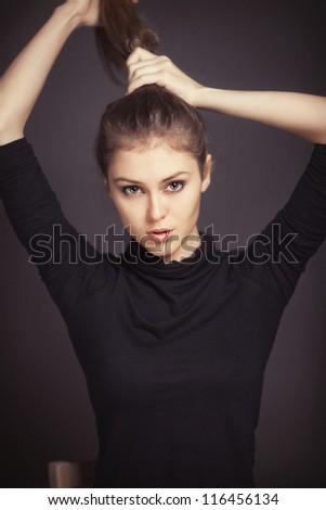 Studio portrait of girl doing hair - stock photo