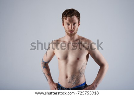 Studio portrait of handsome and confident Caucasian adult male model with stylish trimmed beard and tattooed body demonstrating his perfect sporty torso at camera, holding hands on his waist.