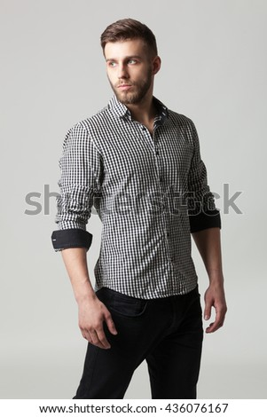 Studio portrait of handsome elegant young man in casual clothes posing against gray background.