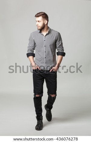 Studio portrait of handsome elegant young man in casual clothes posing against gray background. - stock photo