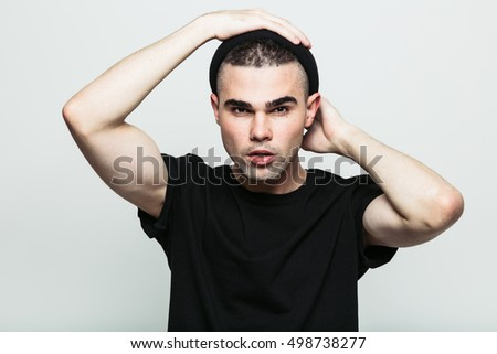 Studio portrait of handsome male model posing at camera on white background.