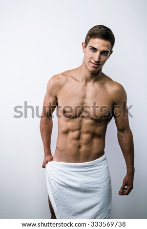 Studio portrait of handsome sexy sporty young man. Muscular man with naked torso and towel on hips looking at camera - stock photo