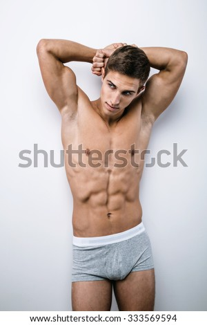 Studio portrait of handsome sexy sporty young man. Muscular man with naked torso wearing grey underwear