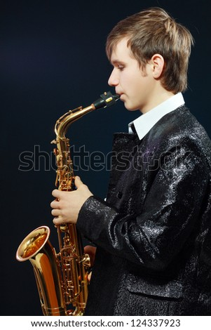 Studio portrait of happy young man with saxophone on dark background.