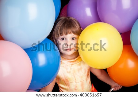 Studio portrait of little Caucasian blond girl with colorful balloons
