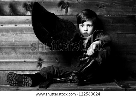 studio portrait of little cowboy holding his hat in hand