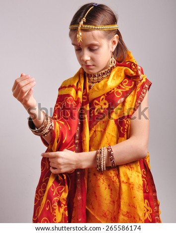 studio portrait of little girl putting on traditional Indian clothing and jeweleries - stock photo