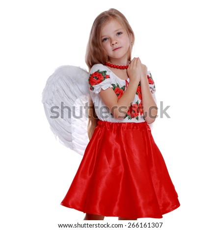 Studio portrait of lovely little ukrainian angelic girl with white wings on Holiday theme/Cheerful little girl in a bright Ukrainian national costume