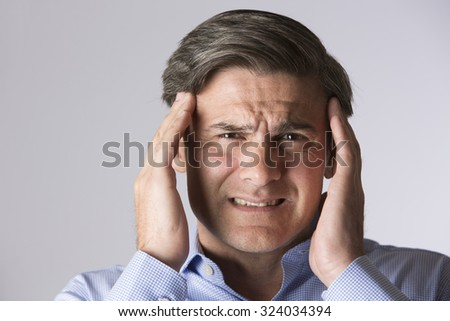 Studio Portrait Of Man Suffering With Headache - stock photo