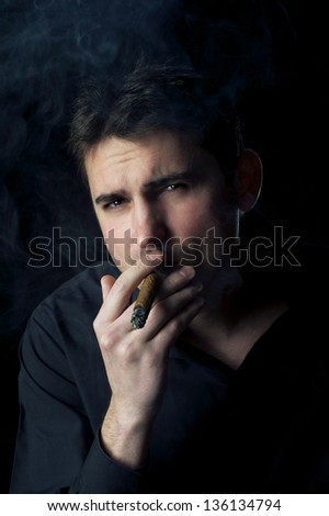 Studio portrait of man with cigar