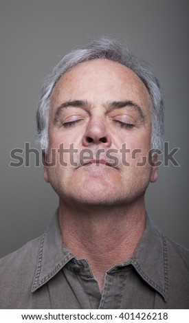 Studio portrait of mature man with eyes closed. - stock photo