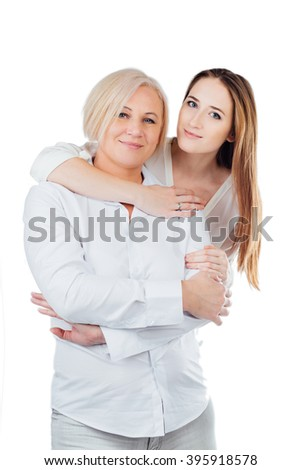 Studio portrait of mother and adult daughter. Daughter in white sweater hugging her mother from behind a white shirt. Isolated white background. Looking at the camera - stock photo