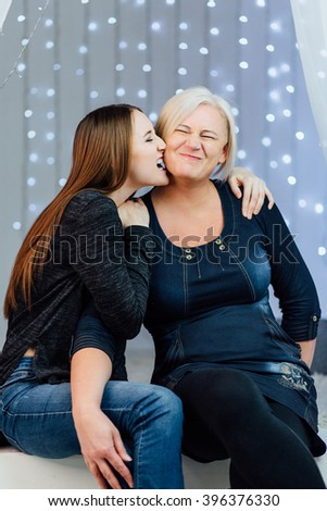 Studio portrait of mother and adult daughter. Daughter mother for biting the cheek, grimacing - stock photo