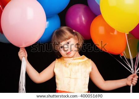 Studio portrait of positive Caucasian blond little girl with colorful balloons - stock photo