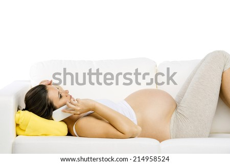 Studio portrait of pregnant woman with digital tablet lying down on sofa isolated on white background - stock photo