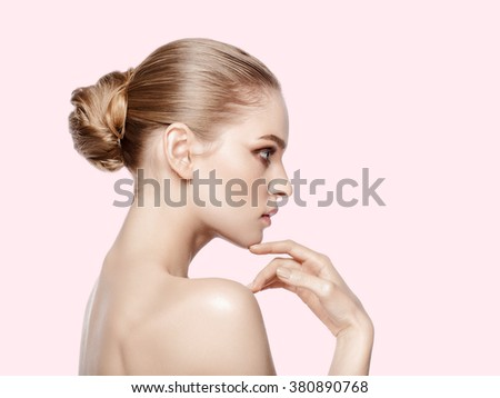 Studio portrait of pretty model with professional makeup and hairdo on pink background. Perfect fresh clean skin. Blue eyes. Blonde hair. Not isolated - stock photo