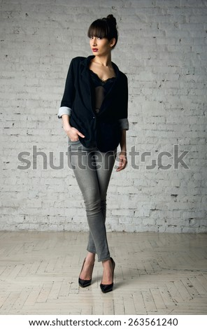 Studio portrait of pretty sexy woman model with beautiful long legs standing wearing denim jeans black lingerie top, jacket, posing looking at camera. White brick white wall background copy space - stock photo
