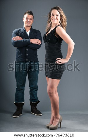 Studio portrait of pretty young couple isolated on grey background