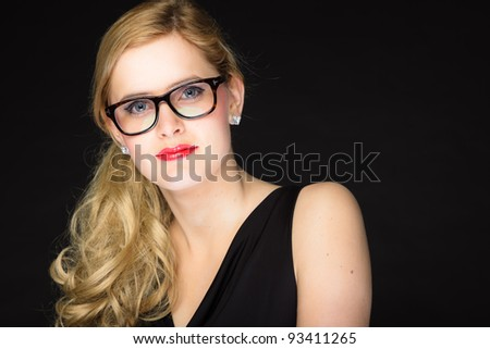 Studio portrait of pretty young woman with red lipstick and long blond hair wearing glasses. Wearing a black dress. Isolated on black background. - stock photo