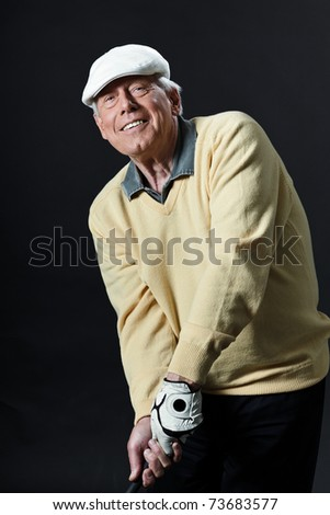 Studio portrait of senior golf man with yellow shirt and white cap making swing with golf club. Black background. - stock photo