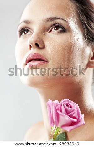 Studio portrait of sensual beautiful woman with rose and water droplets on her face - stock photo