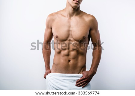 Studio portrait of sexy sporty young man. Muscular man with naked torso and towel on hips