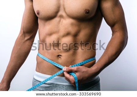 Studio portrait of sexy sporty young man. Muscular man with naked torso wearing grey underwear and holding measuring tape