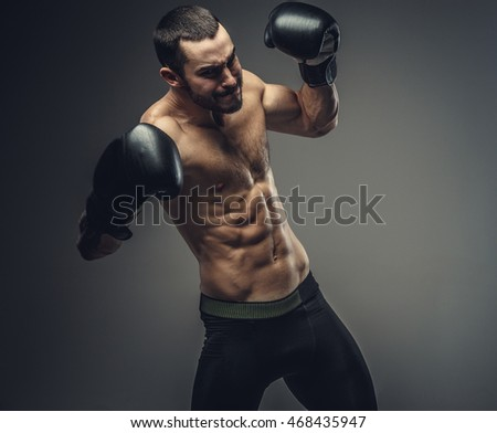 Studio portrait of shirtless male fighter in boxing gloves.