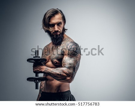 Studio portrait of shirtless tattooed bearded male holds dumbbell on grey vignette background.
