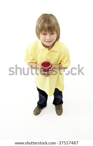 Studio Portrait of Smiling Boy Holding Glass of Fruit Juice