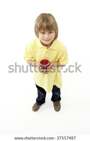 Studio Portrait of Smiling Boy Holding Glass of Fruit Juice - stock photo