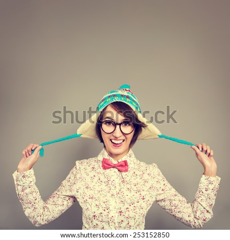 Studio Portrait of Smiling Hipster Girl in Funny Winter Hat Fooling Around and Tease. Copy Space. Instagram Styled Filtered Photo. - stock photo
