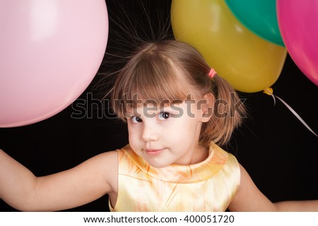 Studio portrait of smiling little Caucasian blond girl with colorful balloons - stock photo