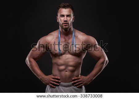 studio portrait of sporty and athletic muscular man isolated on black background - stock photo