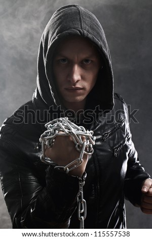 Studio portrait of street fighter with chains over his fist - stock photo