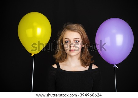 Studio portrait of teenage Caucasian blond girl with yellow and purple balloons over black background - stock photo
