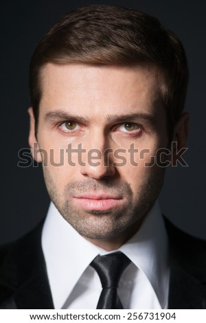 Studio portrait of thinking young business man. In thought. Suit and tie. - stock photo