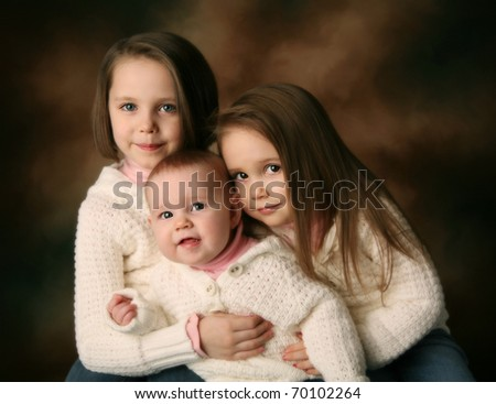 Studio portrait of three cute young sisters hugging each other wearing white cream sweaters on a brown background, baby, toddler, and preschool aged