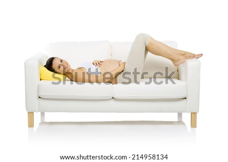 Studio portrait of tired pregnant woman lying down on sofa isolated on white background - stock photo