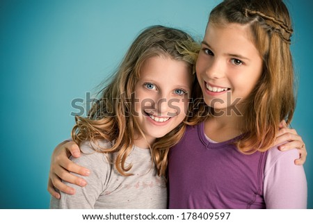 Studio portrait of two cute girls smiling.