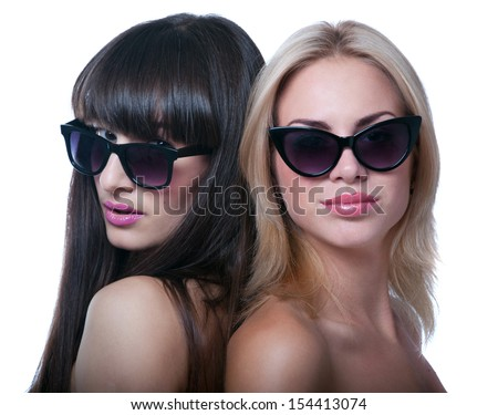 Studio portrait of two young beautiful women models wearing bright pink lipstick, sun glasses, smiling and looking at camera. Isolated on white background