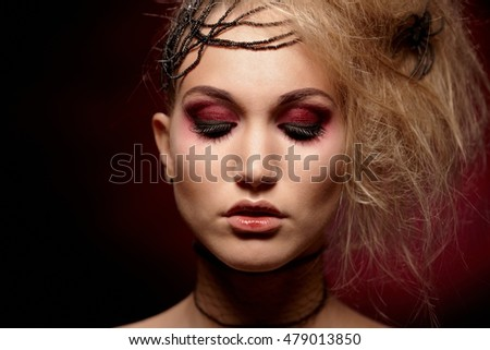 Studio portrait of woman in halloween makeup, black background.