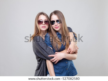 Studio portrait of young and happy twin sisters embracing