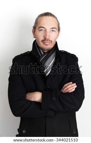 Studio portrait of young Asian man in black coat and woolen scarf, vertical photo over white wall background