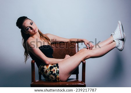 Studio Portrait of Young Attractive Woman sitting on brown leather chair sideways with legs sticking straight up head tilted