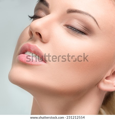 Studio portrait of young beautiful blonde woman with perfect skin - stock photo