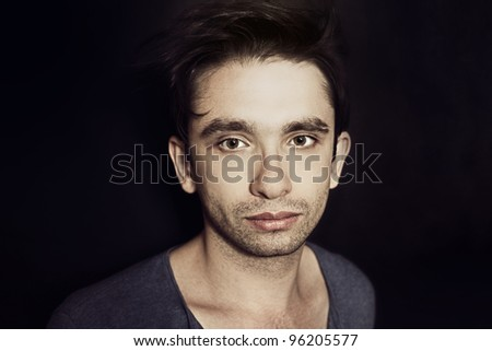 Studio portrait of young beautiful brunette guy with a stylish hair on black background
